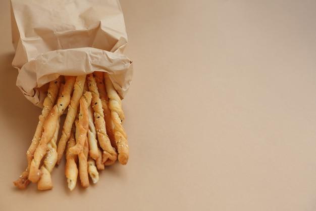 Collation croustillante dans un sac en papier bâtonnets de pain au sésame salé pour une bouchée rapide