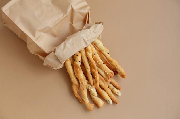 Collation croustillante dans un sac en papier. des gressins pour une bouchée rapide
