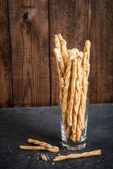 Collation italienne traditionnelle, pain - grizzini. dans la planche à découper de la cuisine. sur une table en pierre sombre, copiez l'espace