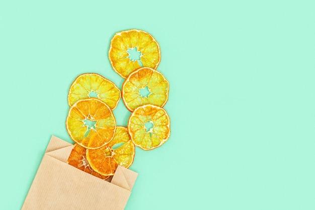 Collation saine. chips de fruits déshydratés maison de mandarine. mandarine sèche dans un emballage en papier.