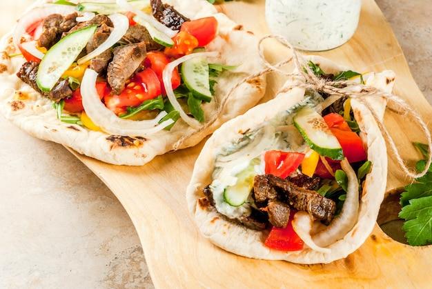 Collation saine, déjeuner. gyros sandwichs enveloppés grecs traditionnels - tortillas, pain pita avec une garniture de légumes, viande de boeuf et sauce tzatziki