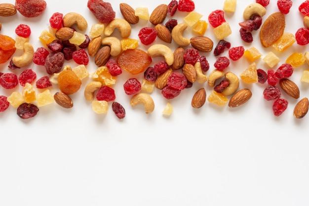 Collation saine: noix mélangées et fruits séchés sur fond blanc d'en haut.