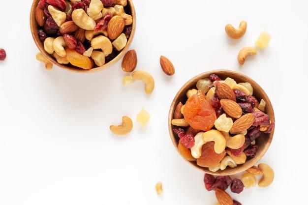 Collation saine: noix mélangées et fruits secs dans un bol en bois sur fond blanc par le haut.
