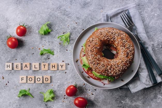 Collation saine nourriture déjeuner. bagel avec avocat, tomate, radis et feuilles vertes.