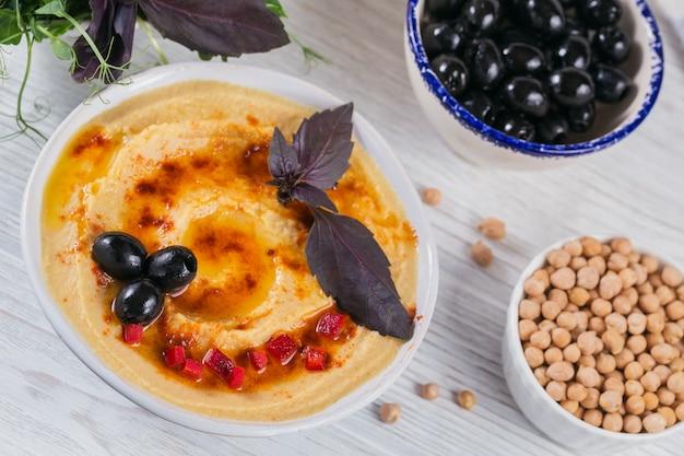 Collation saine de pain croustillant avec houmous, huile d'olive, olives noires et paprika sur une surface en bois blanche.