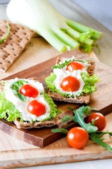 Collation santé à base de craquelin de pain de seigle complet avec seigle, tomates cerises, salade et fromage cottage