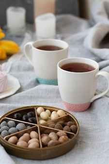 Une collation savoureuse: deux tasses de thé, une assiette de zéphyr et une boîte de bonbons.