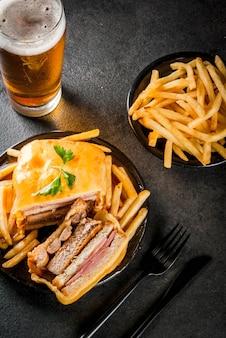 Collation traditionnelle portugaise. sandwich francesinha de pain, fromage, porc, jambon, saucisses, sauce à la bière à la tomate et frites. avec un verre de bière et de pommes de terre. sur tableau noir. espace copie