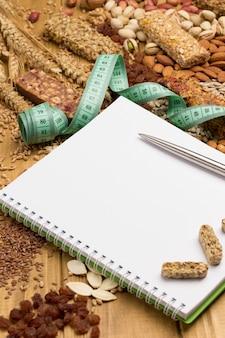 Collation végétalienne équilibrée, barre granola protéinée. noix, graines, cahier de céréales, stylo, ruban à mesurer sur fond en bois.