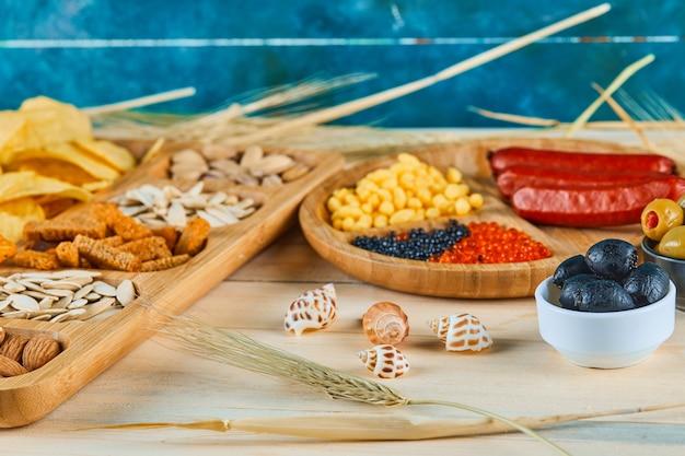 Des collations assorties, une assiette de saucisses, de caviar et d'olives sur une table en bois.