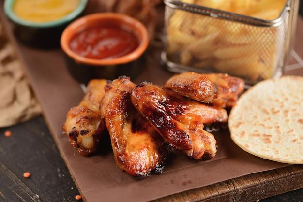 Des collations à la bière. ailes de poulet frites, frites, rondelles d'oignon, fromage en pâte et viande séchée. sur une planche de bois