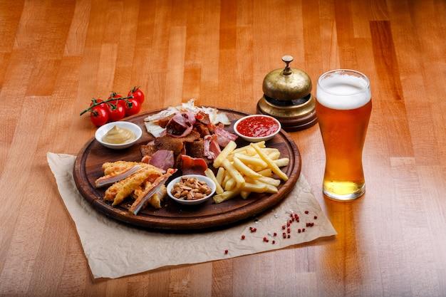 Des collations à la bière ou à l'alcool comprenant de la viande de porc fumée, des frites, du pain frit, des bâtonnets de crabe et des noix