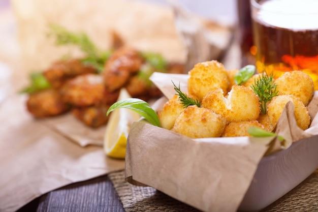 Des collations à la bière. poisson frit et boulettes de fromage au citron et aux légumes verts. des collations à différentes bières.