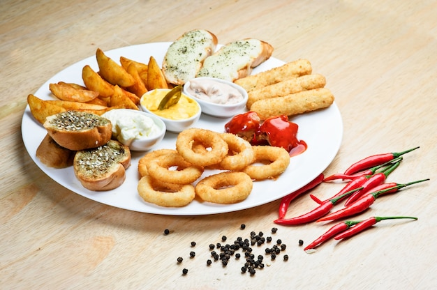 Collations chaudes assorties. fromage rôti, croûtons, rondelles d'oignons au ketchup