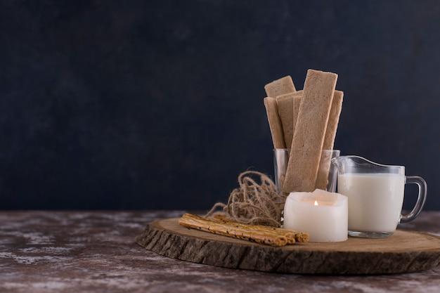 Des collations et des craquelins avec un verre de lait sur une planche en bois avec une bougie blanche de côté.