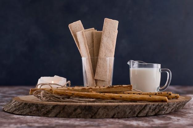 Des collations et des craquelins avec un verre de lait sur une table en marbre sur fond noir.
