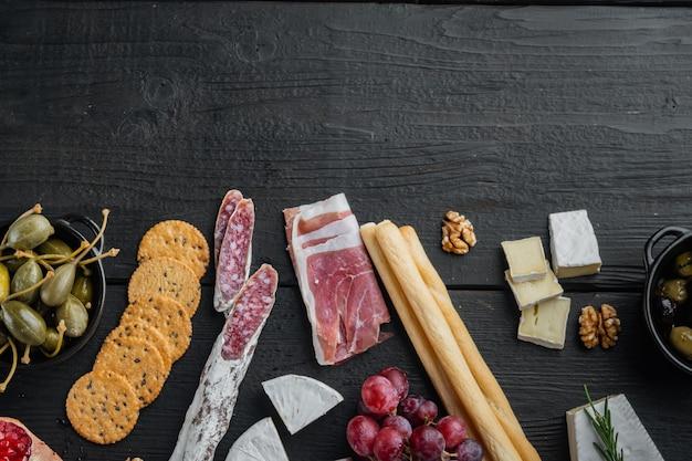 Des collations espagnoles, du fromage à la viande, des herbes, sur une table en bois noire, à plat avec copie espace pour le texte