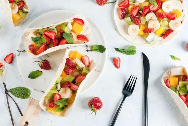 Collations d'été. nourriture pour une fête. tacos aux fruits avec fraises, mangues, bananes, chocolat, menthe. sur une table en béton bleu clair. copier la vue de dessus de l'espace