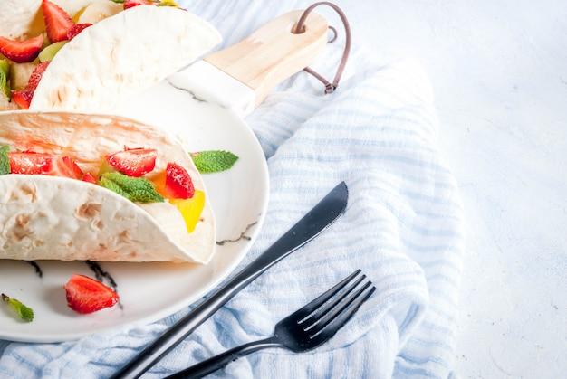 Collations d'été. nourriture pour une fête. tacos aux fruits avec fraises, mangues, bananes, chocolat, menthe. sur une table en béton bleu clair. fond