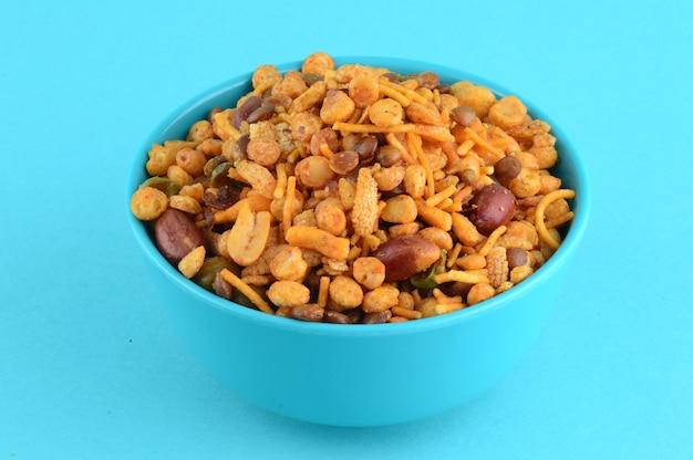 Collations indiennes: mélange (noix rôties avec masala poivre sel, légumineuses, pois verts channa masala dal) dans un bol bleu dans