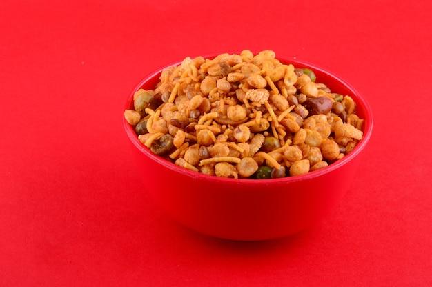 Collations indiennes: mélange (noix rôties avec sel poivre masala, légumineuses, channa masala dal, pois verts) dans un bol rouge sur une surface rouge