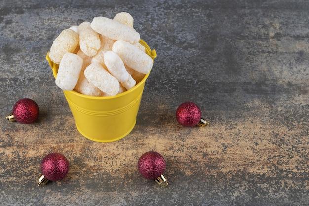 Des collations de maïs empilées dans un seau à côté de boules de noël sur une surface en marbre