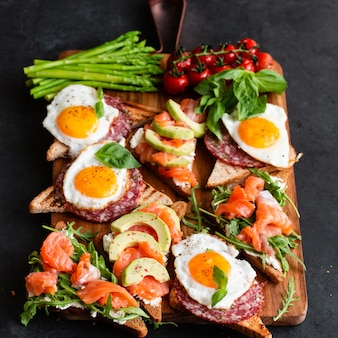 Collations méditerranéennes avec pinceaux, variété de fromages, salami, œufs et saumon sur fond noir