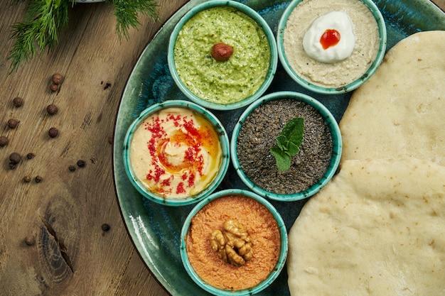 Collations orientales classiques avec pita - meze. mettre dans un petit bol - houmous, pâte de piment fort souvent aux noix, yaourt, pâte d'aubergine.