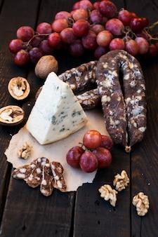 Collations pour le vin, le fromage avec de la moisissure, les raisins roses, les noix et les saucisses sèches séchées