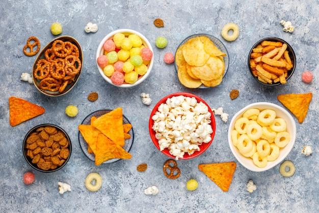Collations salées. bretzels, chips, crackers, pop-corn dans des bols. produits malsains. nourriture mauvaise pour la figure, la peau, le cœur et les dents. assortiment d'aliments riches en glucides