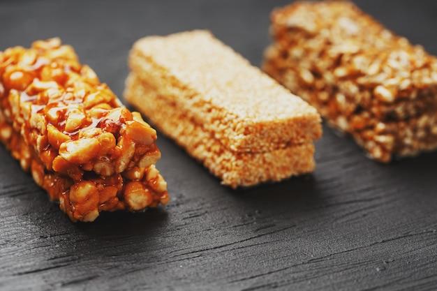 Collations santé. aliments de régime de remise en forme. barre de céréales avec des cacahuètes, du sésame et des graines sur une planche à découper sur une table sombre, barres énergétiques