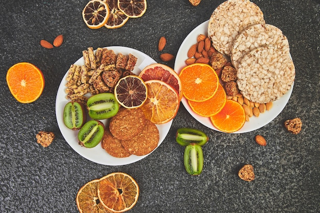 Collations santé - divers types de barres de céréales, céréales, amandes, kiwis, orange séchée