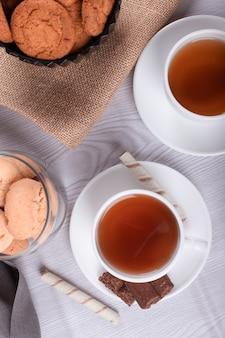 Collations sucrées, tasse de thé sur fond clair