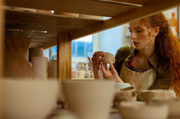 Collecte de pots. belle femme gingembre aux cheveux longs vérifiant une petite tasse d'argile tout en vérifiant les figures finies