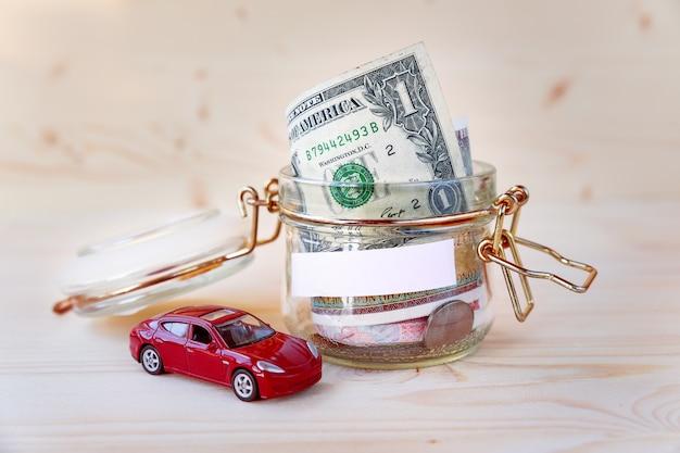 Collecter de l'argent pour une nouvelle voiture. boîte en verre comme tirelire avec épargne en espèces (billets et pièces) et voiture miniature