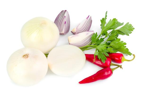 Collection d'ail et d'oignon avec du poivre et du persil isolé sur une surface blanche.