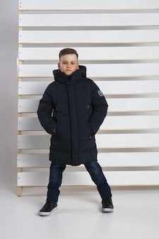 Collection d'automne de vêtements pour enfants et adolescents. vestes et manteaux pour le froid d'automne. les enfants posent sur un fond blanc.