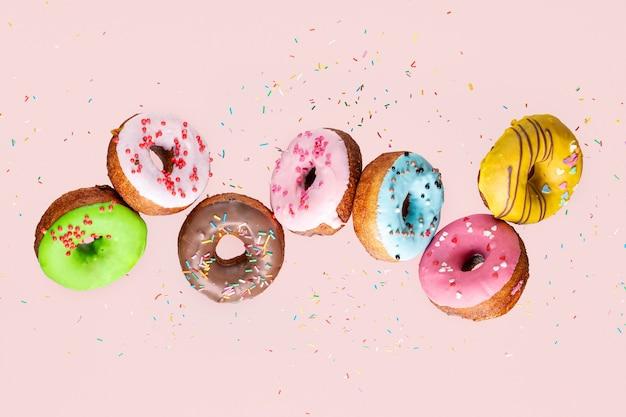 Collection de beignets avec des beignets bleus, roses, verts et jaunes volants sur fond rose