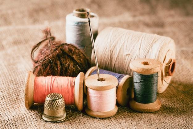 Collection de bobines de fil de couleur avec aiguille et dé à coudre sur toile