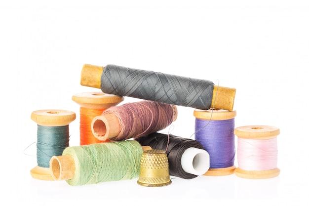 Collection de bobines de fil de couleur avec dé à coudre isolé sur blanc