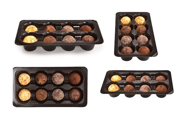 Collection de bonbons au chocolat dans une boîte en plastique.