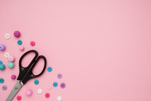 Collection de boutons de couture colorés et de ciseaux avec espace de copie de fond