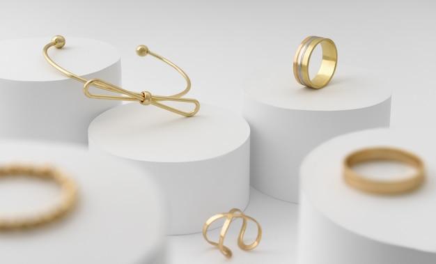 Collection de bracelets et bagues en forme d'arc doré moderne sur une plate-forme de cylindres blancs