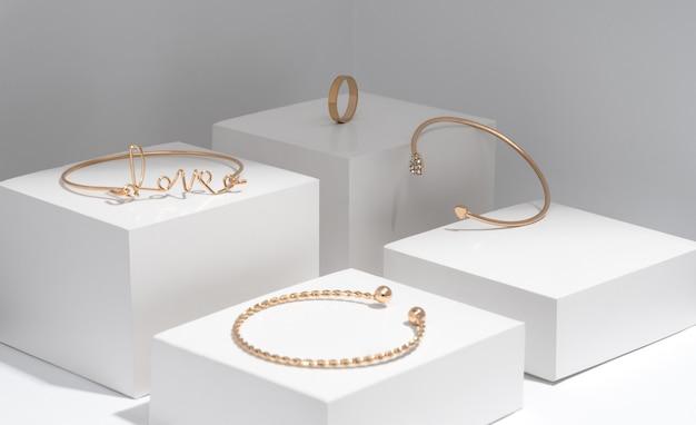 Collection de bracelets dorés en forme de mot d'amour sur blanc géométrique