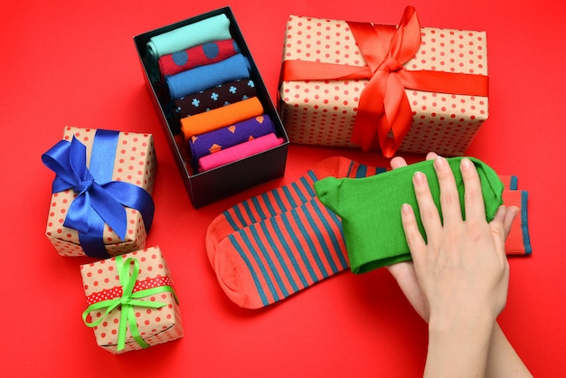 Collection colorée de chaussettes en coton comme cadeau dans les mains de la femme.