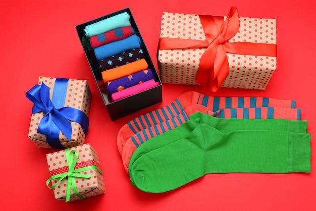 Collection colorée de chaussettes en coton comme cadeau dans les mains de la femme