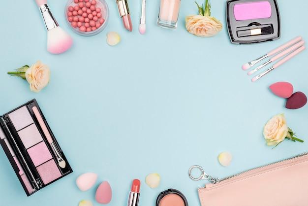 Collection de différents cosmétiques avec espace copie sur fond bleu