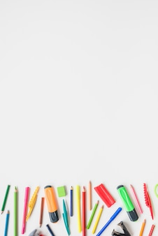 Collection de diverses fournitures scolaires sur un bureau blanc