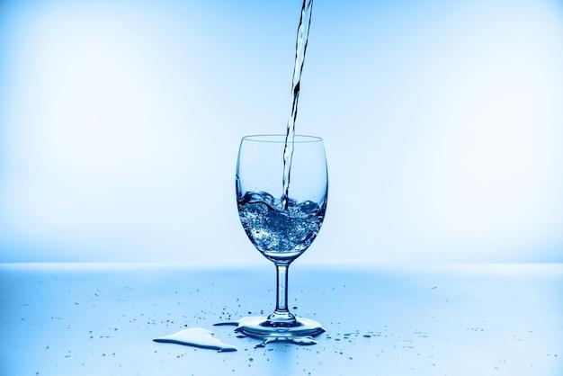 Collection d'éclaboussures d'eau dans un verre à vin isolé sur mur bleu