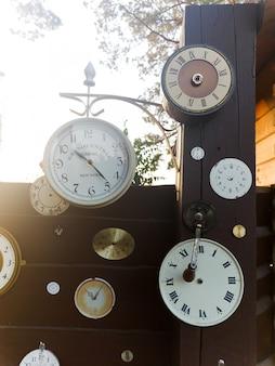 Collection d'horloge vintage suspendue à un vieux mur en bois à l'extérieur avec le soleil